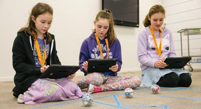 Three girls using tablets to control Sphero