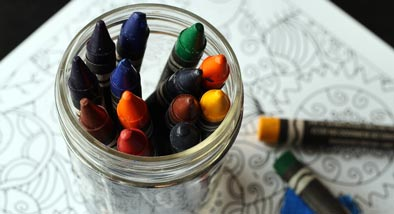 Jar of coloured crayons sitting on colouring in drawing.