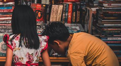 Two kids looking through a pile of books.