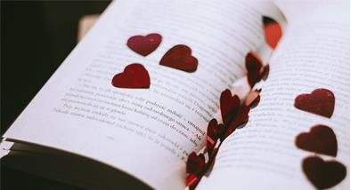 Open book with paper hearts.