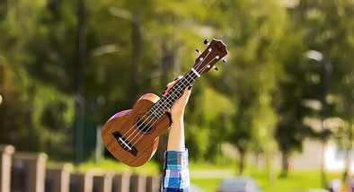 Ukulele being held in the air.
