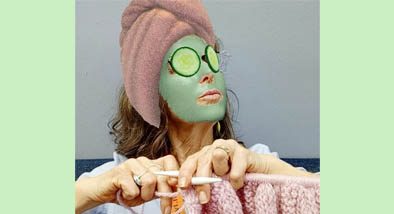 Woman wearing face mask while knitting.