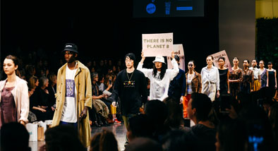 "Fashion show with person holding a sign that says ""There is no Planet B"""