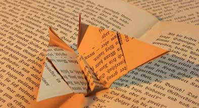Origami butterfly made of a page from a book resting on an open book.
