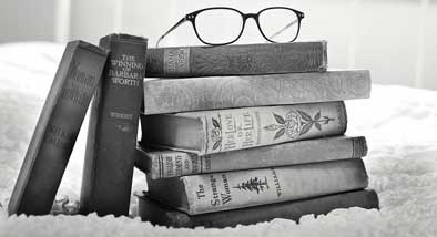 Stack of books on a bed with glasses balancing on top.