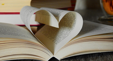 Photograph of an open book with page leaves forming a heart.