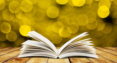 Open book on wooden table with glimmering yellow background.