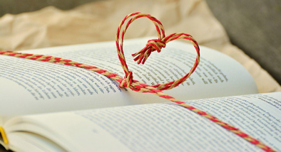 open book with friendship bracelet twined around it in a heart shape.