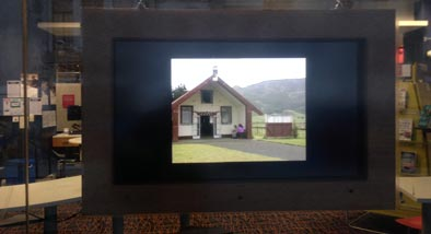Viewfinder exhibition showing framed image of meeting house in window of Central library