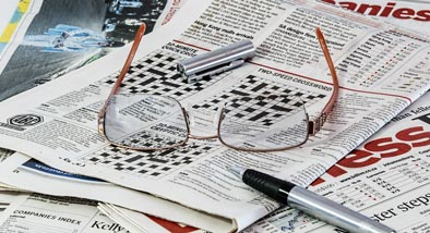 Eyeglasses and pen on pile of crosswords.