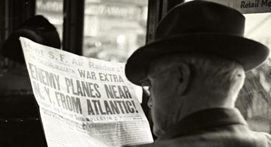 Black and white photograph of man reading newspaper from WW2