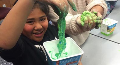 girls holding green slime