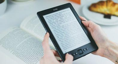A hand holding an eReader with script on the screen