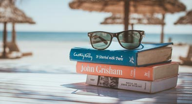 Three books stacked with sunglasses on top by beach