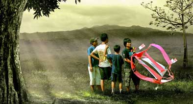 Small group of boys with large complicated kite standing in front of foliage covered mountain.