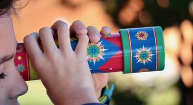 Child holding colourful patterned kaleidoscope up to eye.