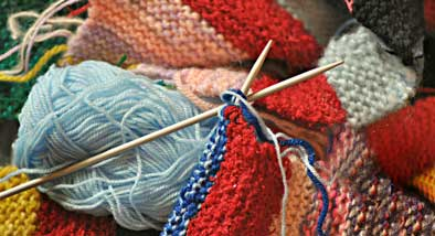 Colourful knitting with balls of red and blue wool.