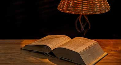 Thick old book open on wooden table in darkened room, illuminated by a wicker light shade.