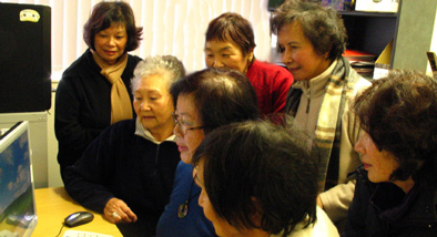 Group of Chinese women gathered around a computer