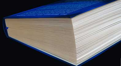 Large blue book on black background, with pages beginning to open.