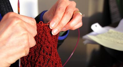 Hands knitting with dark red wool.