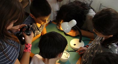 Children gathered around a table with a lamp owrking on electronics