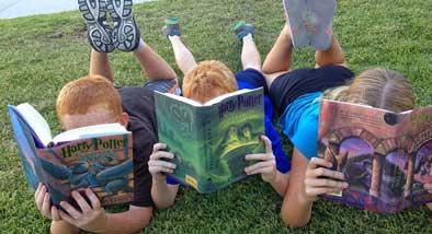 Three children laying on their stomachs on grass, faces hidden by the Harry Potter books they are reading.