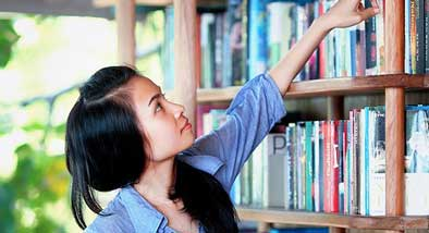 Teen in front of a book shelf