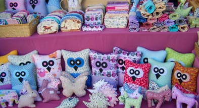 Stuffed owls on shelves next to rolls of cloth.