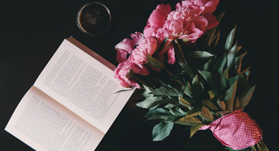 Book open on dark table next to bouquet of pink flowers and a beverage in a glass.