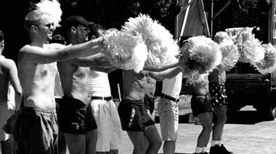 Black and white photo of eight mostly top-less men shaking pompoms. From: Sir George Grey Special Collections, 835-27.